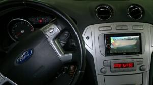 Na ekranie obraz z kamery cofania, przedstawiający fragment naszego parkingu.